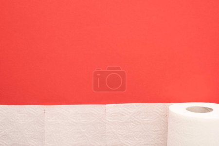 top view of white toilet paper roll on red background with copy space