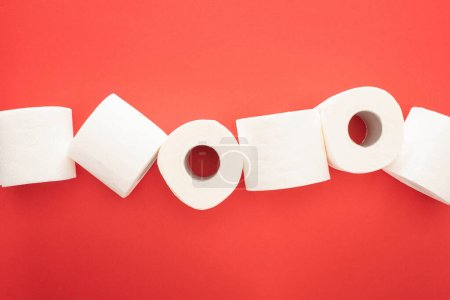 top view of clean toilet paper rolls on red background