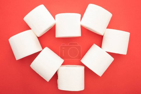 Photo for Top view of white toilet paper rolls arranged in heart on red background - Royalty Free Image