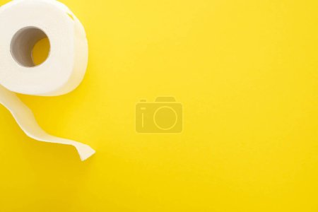 top view of white toilet paper roll on yellow background