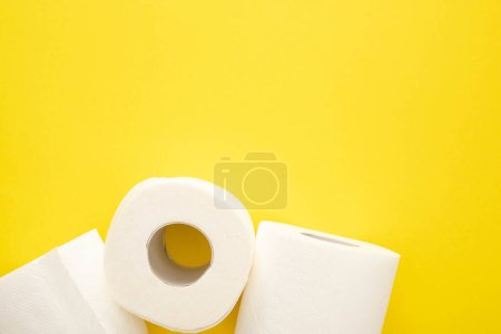 top view of white toilet paper rolls on yellow background
