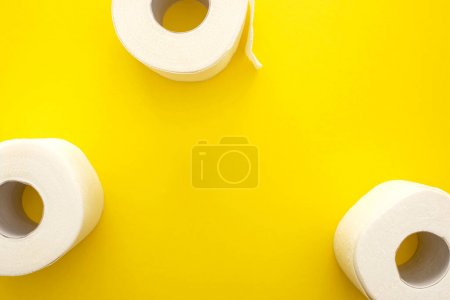 top view of white toilet paper rolls on yellow background with copy space