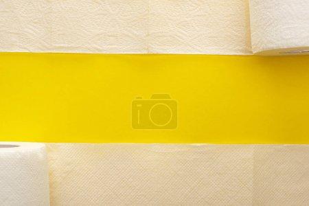Photo pour Vue du dessus du papier hygiénique blanc déroulé sur fond jaune avec espace de copie - image libre de droit