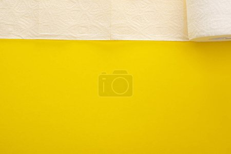 top view of unrolled white toilet paper on yellow background