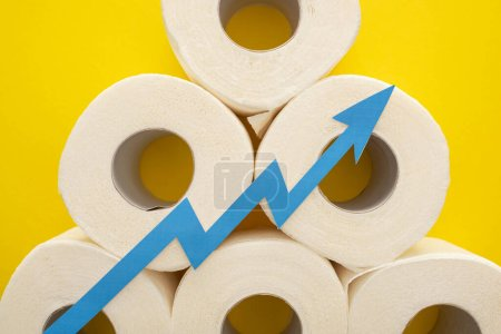 top view of blue arrow on white toilet paper rolls on yellow background