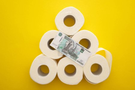 Photo for Top view of white toilet paper rolls arranged in pyramid with russian money on yellow background - Royalty Free Image