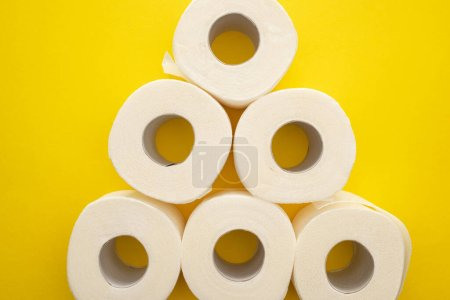 Photo for Top view of white toilet paper rolls arranged in pyramid on yellow background - Royalty Free Image