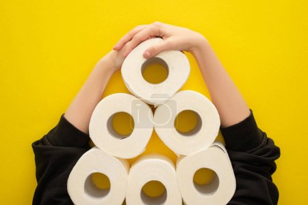 cropped view of woman grabbing white toilet paper rolls arranged in pyramid on yellow background