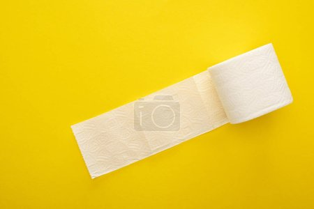 top view of unrolled toilet paper roll on yellow background