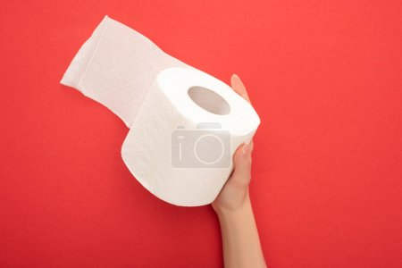 cropped view of woman holding white toilet paper roll on red background