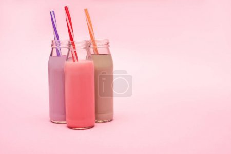 Photo pour Bouteilles de milkshakes aux baies, fraises et chocolat avec pailles à boire sur fond rose - image libre de droit