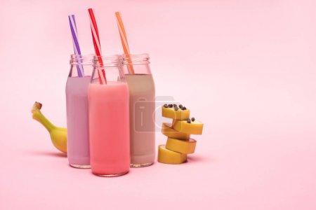Photo pour Bouteilles de milkshakes aux baies, fraises et chocolat avec pailles à boire et banane coupée avec pépites de chocolat sur fond rose - image libre de droit
