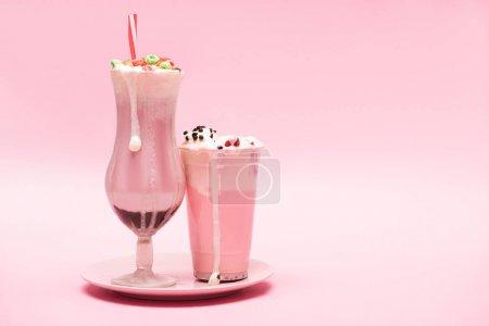 Photo pour Tasse et verre jetables de lait de fraise sur fond rose - image libre de droit