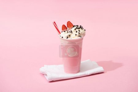 Photo for Disposable cup of milkshake with drinking straw, chocolate chips and strawberry halves on napkins on pink - Royalty Free Image