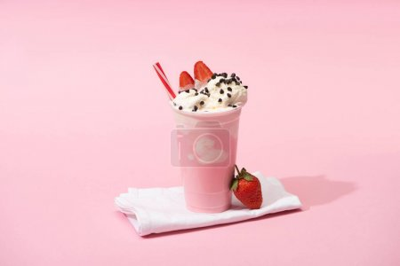 Photo for Disposable cup of milkshake with drinking straw, chocolate chips and strawberries on napkins on pink - Royalty Free Image