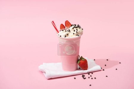 Photo for Disposable cup of milkshake with drinking straw, chocolate chips and strawberries on napkins on pink background - Royalty Free Image