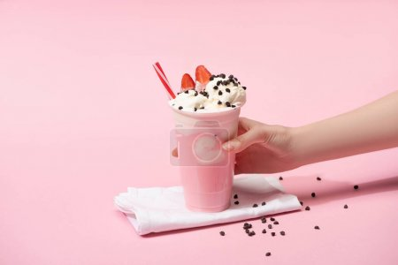 Photo for Cropped view of female hand with disposable cup of milkshake with chocolate morsels and strawberry on napkins on pink - Royalty Free Image