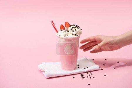 Vue partielle de la main féminine avec tasse jetable de milkshake avec des morceaux de chocolat et fraise sur des serviettes sur rose