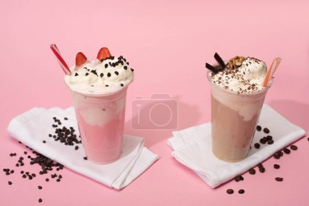 Photo for Disposable cups of chocolate and strawberry milkshakes with coffee grains on napkins on pink background - Royalty Free Image