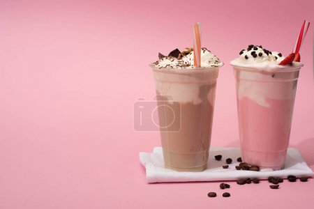 Photo for Disposable cups of chocolate and strawberry milkshakes with drinking straws and coffee grains on napkins on pink - Royalty Free Image