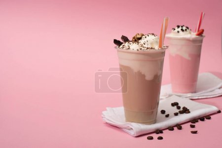 Photo for Selective focus of disposable cups of chocolate and strawberry milkshakes with coffee grains on napkins on pink background - Royalty Free Image