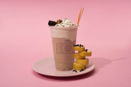 Photo for Disposable cup of milkshake with drinking straw, cut banana and chocolate chips on plate on pink background - Royalty Free Image