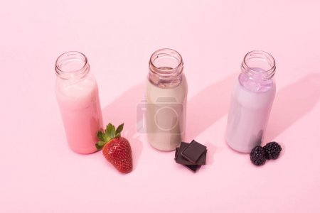 Photo for High angle view of bottles of milkshakes with strawberry, blackberries and pieces of chocolate on pink background - Royalty Free Image