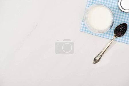Photo for Top view of glass of homemade yogurt and teaspoon with blackberry on plaid fabric on white background - Royalty Free Image