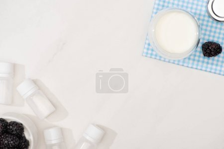 Photo for Top view of glass of yogurt on cloth, containers with starter cultures and blackberries on white background - Royalty Free Image