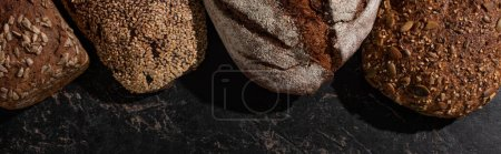Photo for Top view of fresh baked whole grain bread on stone black surface, panoramic shot - Royalty Free Image