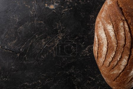 Photo for Top view of fresh baked brown bread loaf on stone black surface - Royalty Free Image