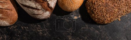 Photo for Top view of fresh baked bread on stone black surface, panoramic shot - Royalty Free Image