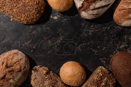 Photo for Top view of fresh baked bread and buns on stone black surface - Royalty Free Image
