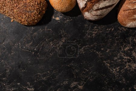 Photo for Top view of fresh baked bread on stone black surface - Royalty Free Image
