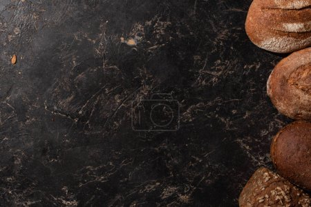 Photo for Top view of fresh baked whole grain bread on stone black surface - Royalty Free Image