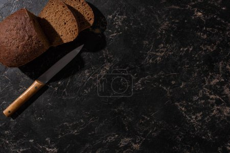 Photo for Top view of fresh cut loaf of brown bread with knife on stone black surface - Royalty Free Image