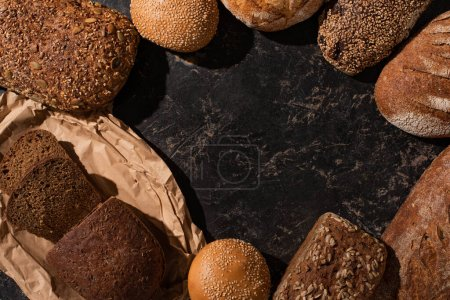 top view of fresh cut and whole bread on stone black surface
