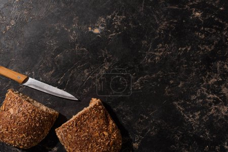 Photo pour Vue du dessus du pain coupé à grains entiers avec couteau sur la surface noire de pierre - image libre de droit