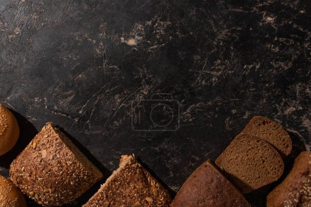 Photo for Top view of cut whole grain bread on stone black surface - Royalty Free Image