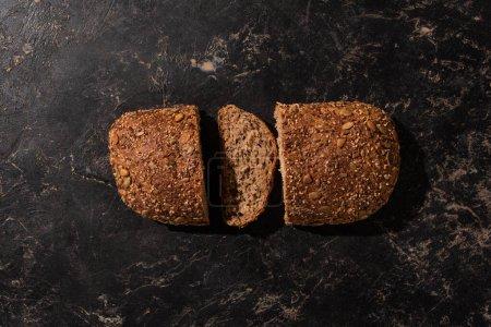Photo pour Vue du dessus du pain coupé à grains entiers sur la surface noire de pierre - image libre de droit