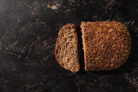 Photo pour Top view of cut whole grain bread on stone black surface - image libre de droit