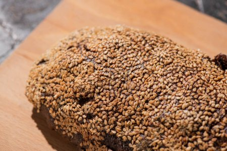 Photo pour Pain noir frais cuit au four avec sésame sur planche à découper - image libre de droit