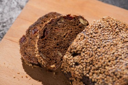 fresh baked black bread with sesame on cutting board