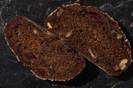 Photo for Top view of fresh baked black bread slices with nuts on stone black surface - Royalty Free Image