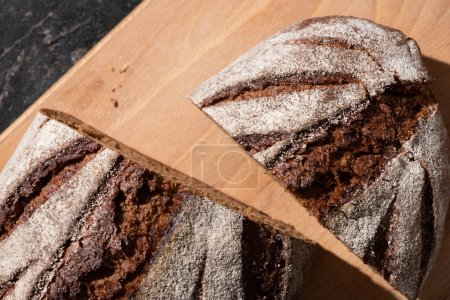 top view of fresh baked cut brown bread on cutting board