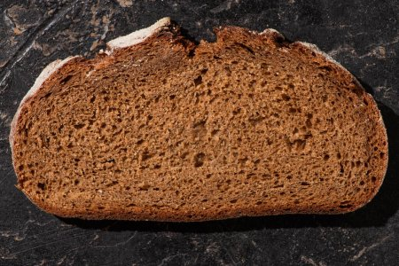 top view of brown bread slice on stone black surface