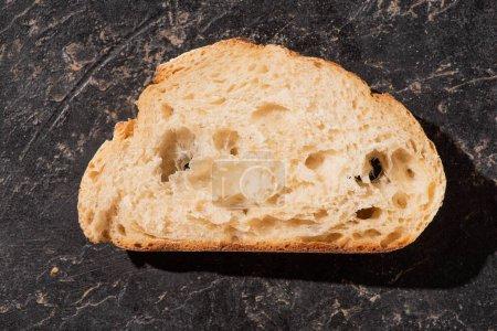 Photo pour Vue de dessus de tranche de pain blanc cuit au four frais sur la surface noire de pierre - image libre de droit