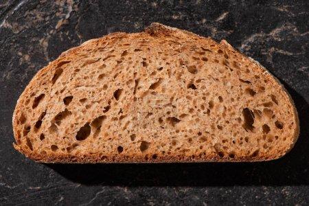 Photo pour Vue de dessus de tranche de pain brun sur la surface noire de pierre - image libre de droit