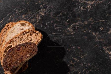 Photo pour Vue de dessus des tranches de pain fraîches cuites au four sur la surface noire de pierre - image libre de droit