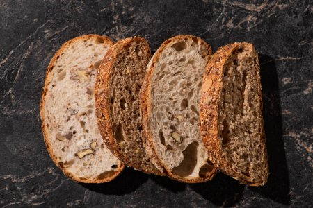 Photo for Top view of fresh baked bread slices on stone black surface - Royalty Free Image
